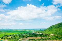 Paisagem da vista superior do prado verde com céu azul e montanha em Imagem de Stock