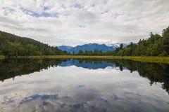 Paisagem de Matheson do lago da reflexão de espelho calma pura da água, cumes do sul na costa oeste da ilha sul, Nova Zelândia imagens de stock royalty free