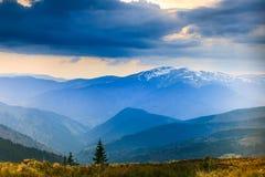Paisagem de partes superiores da montanha enevoada e do céu dramático da noite na distância Fotografia de Stock Royalty Free