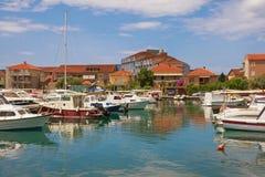 Paisagem de Sunny Mediterranean com os barcos de pesca no porto Montenegro, cidade de Tivat foto de stock