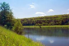 Paisagem de um rio, de uns montes gramíneos e de um vale com árvores Imagem de Stock Royalty Free