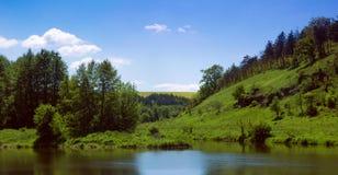 Paisagem de um rio, de uns montes gramíneos verdes com árvores e de um céu Foto de Stock Royalty Free