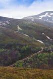Paisagem de uma estrada nas montanhas e nos montes com árvores e meltin Fotos de Stock Royalty Free