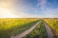 Paisagem de uma estrada de terra em um campo no por do sol, esticando na distância fotos de stock
