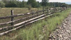 Paisagem do campo do Transcarpathia, Ucrânia Ande ao longo da estrada rochoso ao longo da cerca de madeira das placas vídeos de arquivo