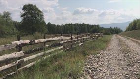 Paisagem do campo do Transcarpathia, Ucrânia Ande ao longo da estrada rochoso ao longo da cerca de madeira das placas video estoque