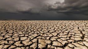 Paisagem do deserto com terra rachada sob nuvens de tempestade ilustração royalty free