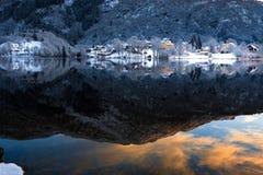 Paisagem do inverno com montanhas nevados, nuvens coloridas, reflexão do lago no por do sol imagem de stock royalty free