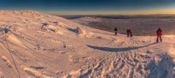 Paisagem do inverno com os caminhantes nas montanhas Foto de Stock