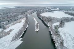 Paisagem do inverno com um rio que corre através da floresta do inverno imagens de stock