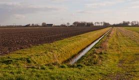 Paisagem do inverno com uma vala e um campo arado Imagem de Stock