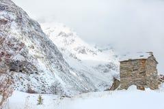 Paisagem do inverno da montanha na borda de um Highland Village com baixas nuvens e reflexões do sol foto de stock