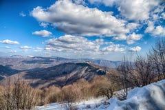 Paisagem do inverno da neve sob um céu azul com nuvens, Itália fotografia de stock royalty free