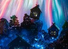 Paisagem do inverno da noite com cabanas e fogos-de-artifício imagem de stock