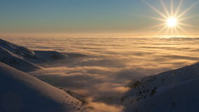 Paisagem do inverno em montanhas Carpathian Por do sol bonito acima das nuvens