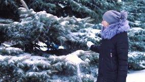 A paisagem do inverno, tiro do lento-movimento, a neve cai lentamente no parque do inverno, a menina anda entre o coberto de neve filme