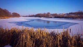 Paisagem do inverno Um gelo-furo no rio coberto com o gelo Imagem de Stock Royalty Free