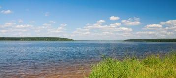 Paisagem do lago com montes e o céu nebuloso azul Imagem de Stock Royalty Free