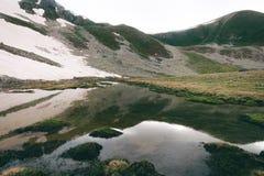 Paisagem do lago highlands com reflexão da água, os montes verdes e a neve foto de stock
