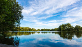 Paisagem do lago summer com árvores e o arbusto verdes, Woking, Surrey fotografia de stock
