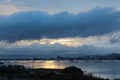 Paisagem do mar e do nascer do sol tormentoso sobre a cidade imagens de stock royalty free