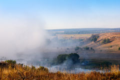Paisagem do montes, árvores, céu e rio amarelos com névoa densa Fotografia de Stock