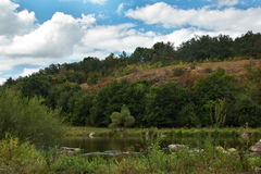Paisagem do montes, árvores, rio e céu gramíneos verdes Foto de Stock Royalty Free