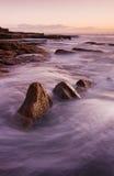 Paisagem do nascer do sol do oceano com nuvens e rochas de ondas Fotos de Stock Royalty Free