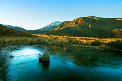 Paisagem do nascer do sol da manhã nas montanhas gelados, nos raios dourados do sol que brilham nos montes e no pico vulcânico co imagem de stock royalty free