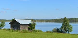 Paisagem do norte do verão com o celeiro na costa do lago da floresta finland imagens de stock