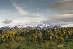 Paisagem do outono com montanhas cobertos de neve, as folhas coloridas e o céu com nuvens especiais Fotografia de Stock Royalty Free