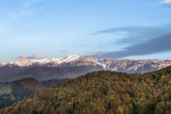 Paisagem do outono com montanhas cobertos de neve, as folhas coloridas e o céu com nuvens especiais Imagens de Stock