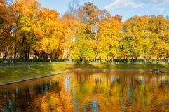 Paisagem do outono - lagoa de Karpiev no jardim do verão com os povos de passeio em St Petersburg, Rússia Fotografia de Stock Royalty Free