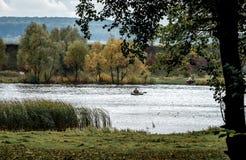 Paisagem do outono que negligencia o rio e as árvores nas costas foto de stock