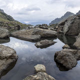 Paisagem do panorama com um lago nas montanhas, nas rochas enormes e nas pedras na costa e na reflexão das nuvens Imagens de Stock