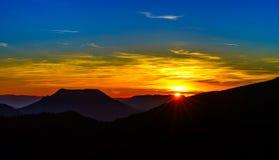 Paisagem do por do sol com as silhuetas das montanhas e vívido idílico Fotos de Stock Royalty Free