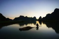 Paisagem do por do sol com pesca do pescador no lago e na montanha em Cao Bang, Vietname fotos de stock