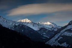 Paisagem do sol que brilha em superior da montanha coberto pela neve Fotos de Stock