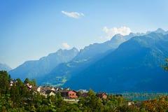 A paisagem do verão com casas pequenas aproxima montanhas Imagens de Stock Royalty Free
