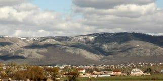 Paisagem e vila da montanha no vale, nos montes, na Crimeia Simferopol, nas regiões do recurso, no céu e nas nuvens, campos e gra fotos de stock