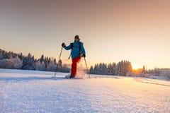Paisagem ensolarada do inverno com o homem em sapatos de neve Foto de Stock Royalty Free