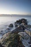 Paisagem impressionante do nascer do sol sobre rochas no mar Imagens de Stock Royalty Free