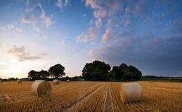 Paisagem impressionante do por do sol do verão sobre o campo de pacotes de feno Foto de Stock Royalty Free