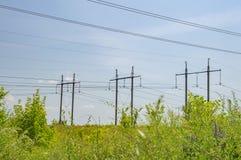 Paisagem industrial - linha de transmissão de energia de alta tensão contra um céu azul foto de stock royalty free