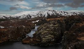 Paisagem islandêsa típica: O parque nacional de Thingvellir, rios, campos de lava cobriu com a neve contra o contexto das montanh fotos de stock