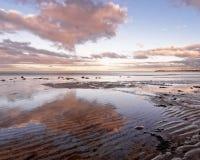 Paisagem litoral com reforços da areia e as nuvens coloridas fotografia de stock