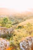 A paisagem magnífica das rochas cobertos de vegetação com a grama verde e desce com o por do sol Fotografia de Stock Royalty Free