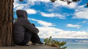 Paisagem A menina em um hoodie senta, e contempla o céu 4k, lapso de tempo filme
