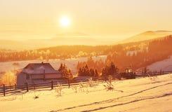 A paisagem misteriosa do inverno é montanhas majestosas no inverno Por do sol fantástico Casas da gravação na neve foto imagem de stock