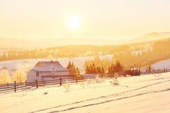 A paisagem misteriosa do inverno é montanhas majestosas no inverno Por do sol fantástico Casas da gravação na neve foto imagens de stock